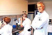 Successful scientist with two female assistants working in background on microscope