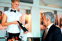 Happy young waitress at restaurant offering a bottle of wine to a mature man