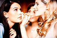 Three Young Women Putting on Make-Up