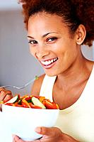Closeup of pretty African American woman eating vegetable salad