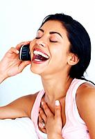 Closeup of beautiful young woman laughing while using cell phone