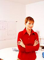 Businesswoman Wearing Red Blouse Standing with Crossed Arms in Office