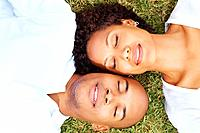 Top view of beautiful young couple sleeping on grass with their heads together