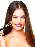 Closeup of glamorous young woman applying blusher on white background