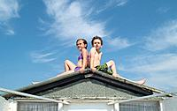 Girl and Boy Sitting on Beach Hut Roof