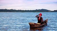 Muscular young fisherman riding his boat on Lake Kivu, Uganda, Entebbe