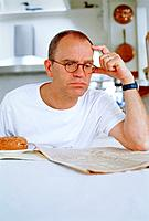 Mature man reading newspaper in kitchen