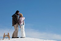 kissing couple with toboggn standing in snow