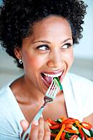 Closeup of beautiful African American woman eating fresh salad while looking away