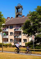 winding tower of the coal mine Auguste Victoria Schacht 4 looming behind a residental building, Germany, North Rhine_Westphalia, Ruhr Area, Marl