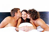 Two men kissing woman in bed