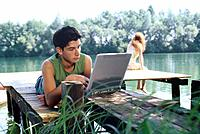 Young man lying on jetty using laptop, woman in the background