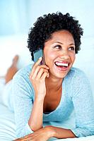 Lovely African American woman laughing while talking on mobile phone on couch