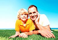 Portrait of a happy young boy with his father lying on a green meadow against sky