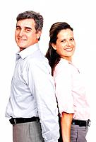 Portrait of successful business couple standing back to back on white background