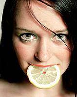 Woman with slice of lemon in the mouth