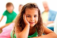 Closeup portrait of cute girl relaxing with family sitting in the background