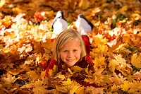 little girl lying in autumn foliage
