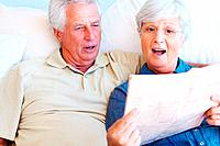Senior couple sitting together on sofa with woman reading newspaper