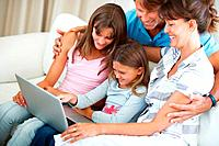 Family of four sitting on a sofa using laptop and smiling