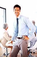 Portrait of a relaxed businessman standing in front of his team in a presentation at office