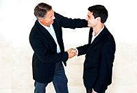 High angle view of business men shaking hands and smiling