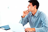 Thoughtful young business man using laptop and looking away