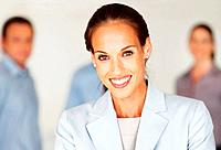 Closeup portrait of female boss smiling with colleagues in background