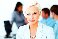 Beautiful blond businesswoman at office with colleagues blurred in background