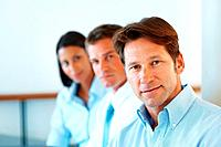 Portrait of a confident young businessman sitting with his business team at office