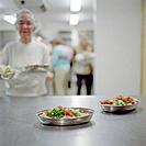 Two Plates with Vegetables, in Background Old Ladies