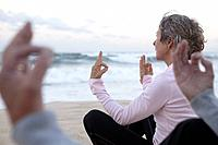 Elderly Couple Meditating on the Beach