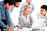 Group of business people with their female leader looking at laptop in office