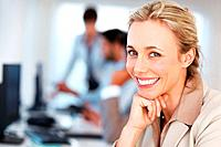 Closeup of cute business woman with hand on chin and smiling with colleagues in blurred background