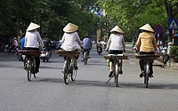 Thre women in conical hats on bicycles Hanoi Vietnam