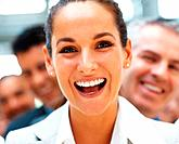 Pretty businesswoman laughing with smiling team behind her