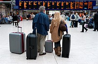 Man and woman with suitcases waiting at Glasgow Central railway station, watching the destination boards, Glasgow, Scotland, UK