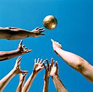 Hands Reaching for Golden Soccer Ball