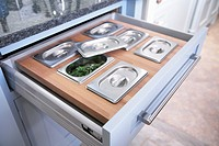 Open drawer with compartments used to store herbs and spices