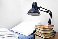 bedside lamp and piled books in bedroom