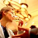 Young Woman Drinking Wine in Bar
