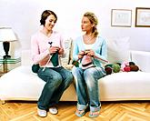 Two Young Women Sitting on Sofa Knitting