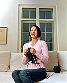 Laughing Young Woman Sitting on Sofa Knitting
