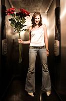 Young Woman Holding Large Bouquet in Elevator
