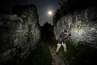 photographer in the castle ruin of Dvigrad at full moon searching geckos, Croatia, Dvigrad