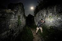photographer in the castle ruin of Dvigrad at full moon searching geckos, Croatia, Dvigrad