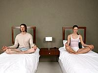 Couple Meditating on Separate Beds