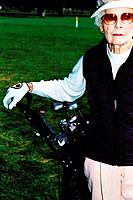 Golfer Resting Arm on Her Clubs