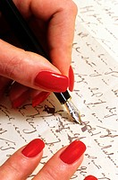 hands of a woman with artificial red fingernails writing a letter with golden ink