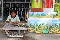 Artist Wayan Rana, painting eggs, outside his shop in Sebali Village, near Ubud  Bali, Indonesia